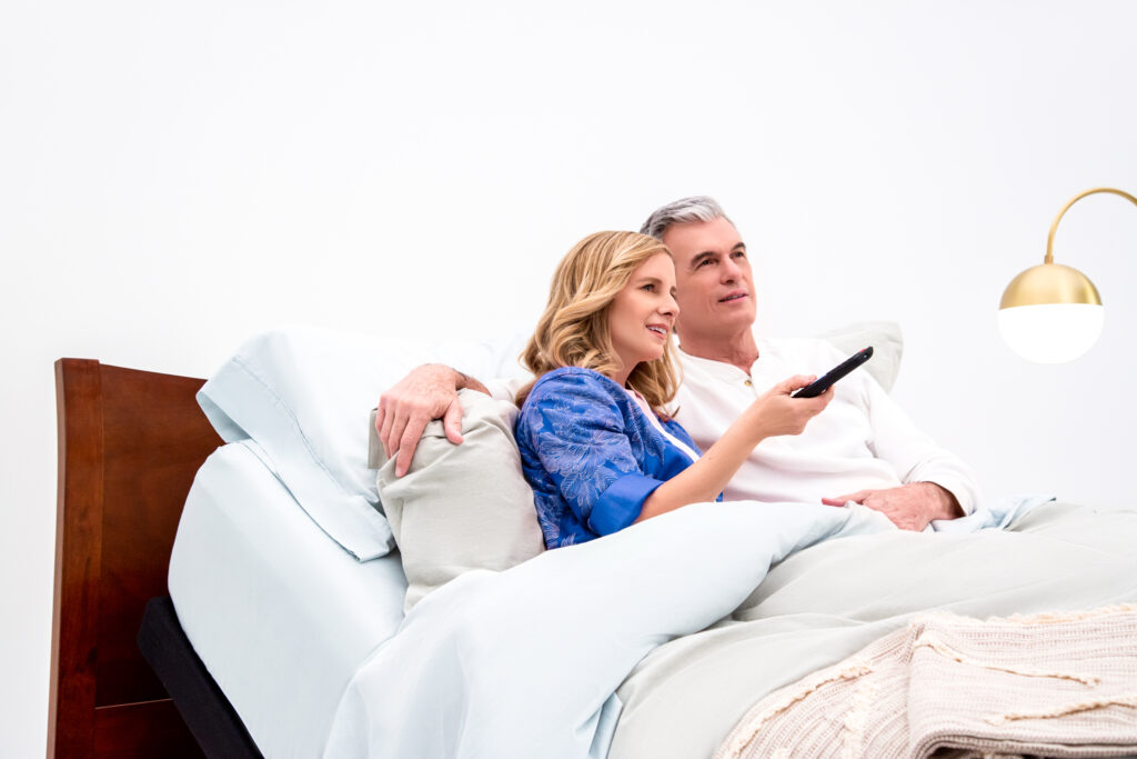 A couple watches tv on their adjustable bed, sitting up comfortably and supported by their mattress.