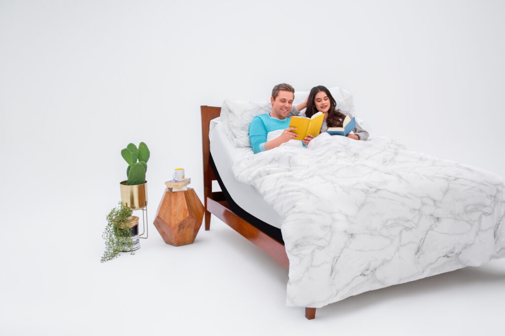 A couple reads on their adjustable bed, sitting up comfortably and supported by their mattress.
